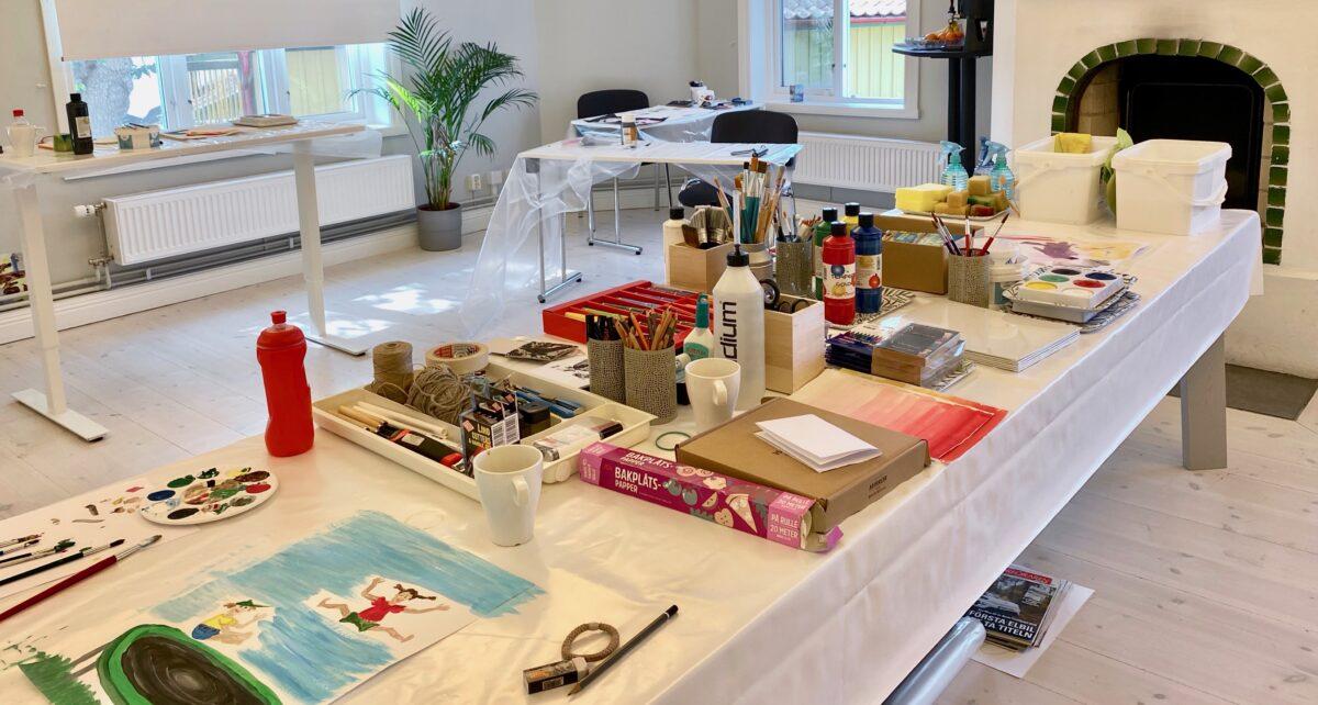 Uppdukat bord med olika målarmaterial. Workshopen har börjat.