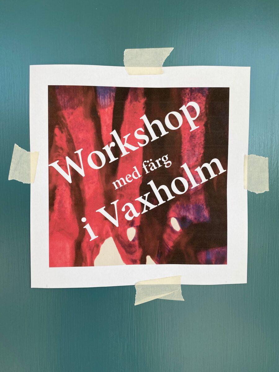 """En papperslapp med skylten """"Workshop med färg i Vaxholm"""" upptejpad på en dörr."""